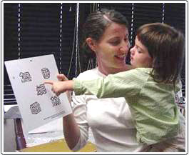 Pre-literate child choosing Wright figure during visual acuity testing. The image is on a corresponding chart held by the examiner. The child selects the image that matches the one being pointed to by the tester.